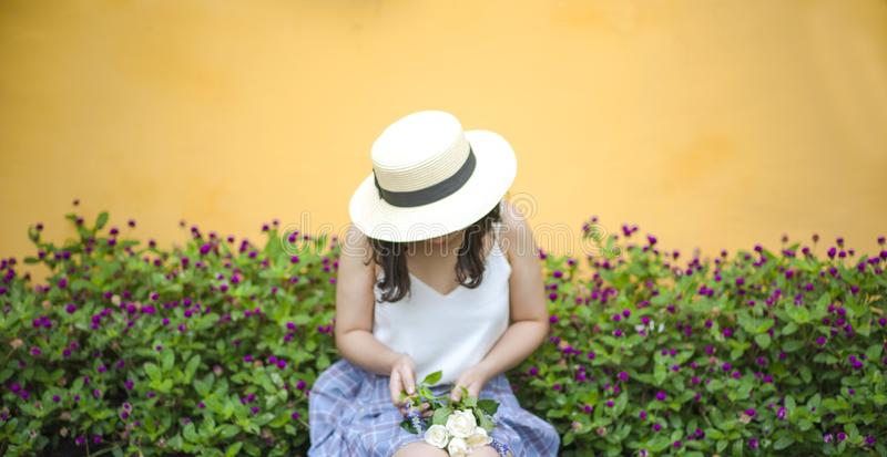 Woman Holding Bunch of White Roses While Sitting Near Flower Fields stock photo