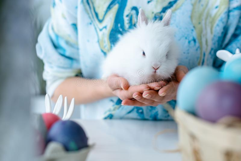 Woman holding bunny by colored Easter eggs on table royalty free stock image