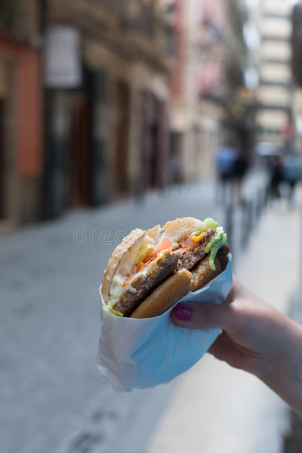 SA hand holding a hamburger in hands. Summer. A woman holding a burger. Summer time in the street of the old city. Tasty hamburger royalty free stock images