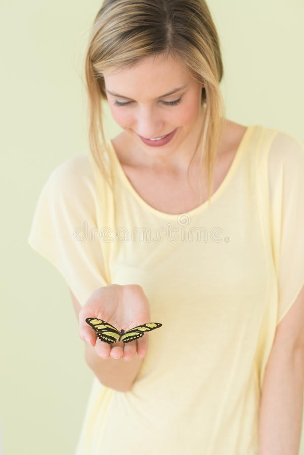 Woman Holding Butterfly In Palm Against Colored Background Royalty Free Stock Image