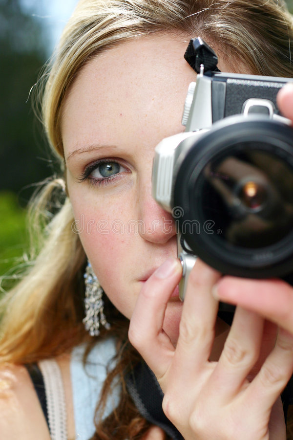 Woman holding camera. Young woman holding and looking into a camera