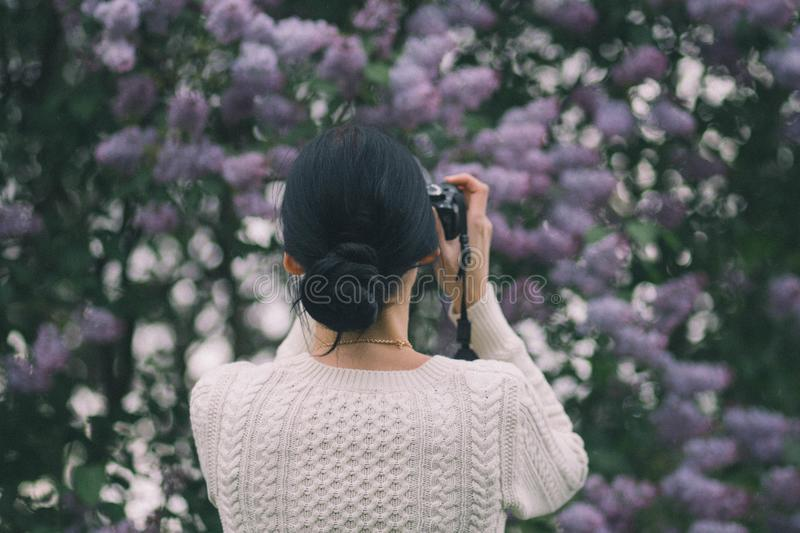 Woman Holding Camera Taking Photos of Flowers royalty free stock photo