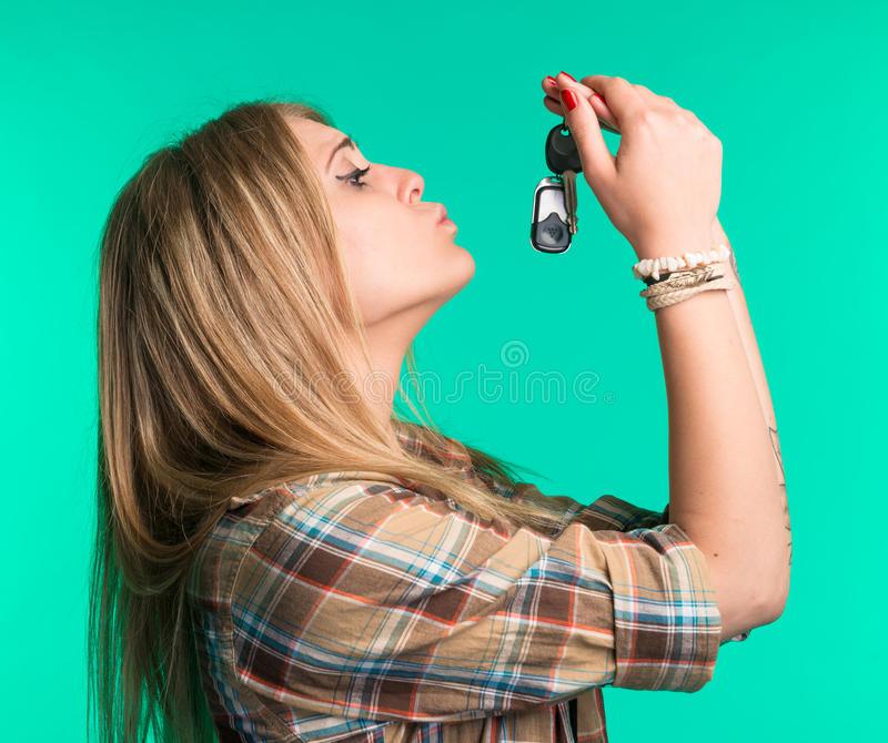 Woman holding car keys. On a green background stock photography