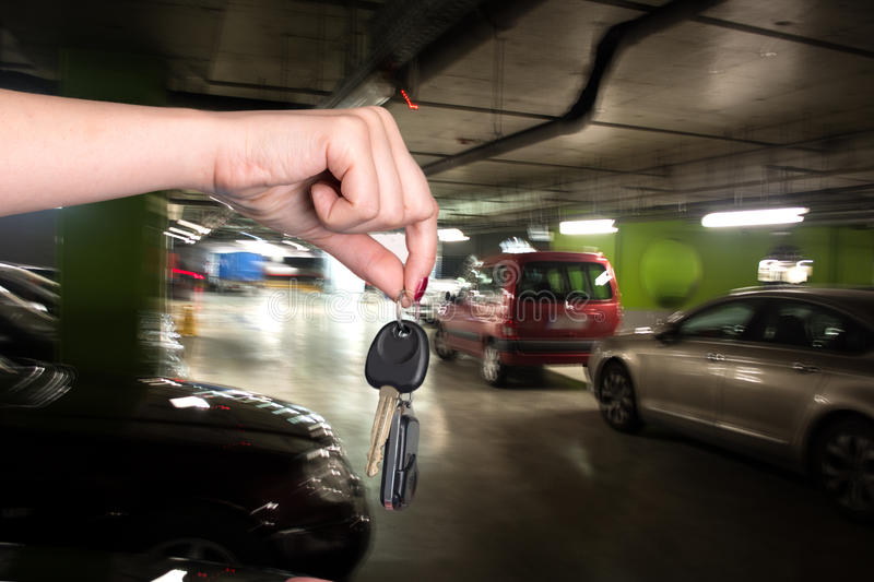 Woman holding car keys. In the parking garage royalty free stock image