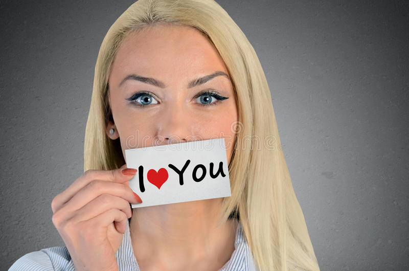Woman holding card with I love you word. Beautiful woman holding card with I love you word royalty free stock photos
