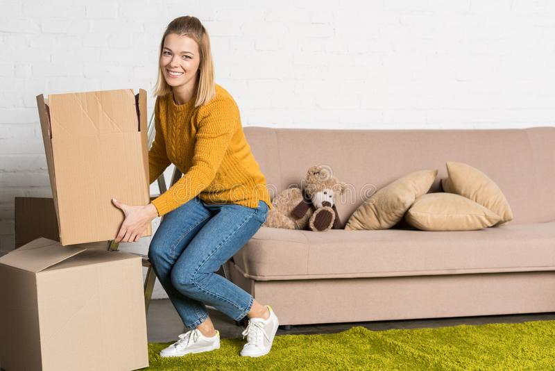 woman holding cardboard box and smiling at camera royalty free stock images
