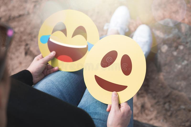 Woman holding 2 cardboard emoticons in hand. royalty free stock photos
