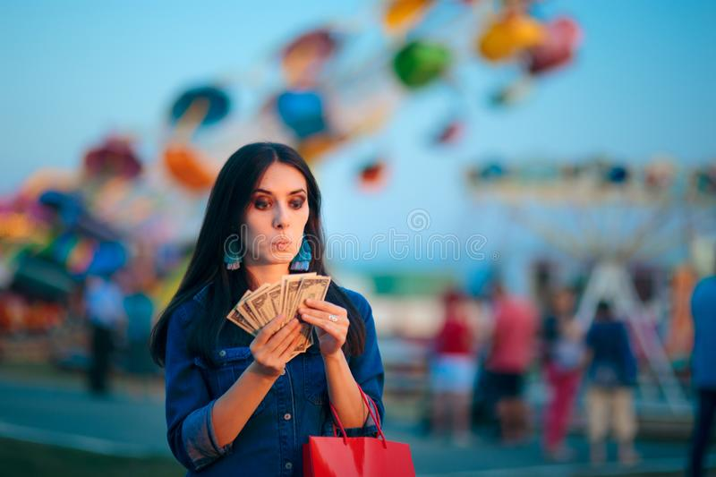 Woman Holding Cash Money at Summer Funfair. Millennial holding banknotes after lucky win in amusement park games royalty free stock photos