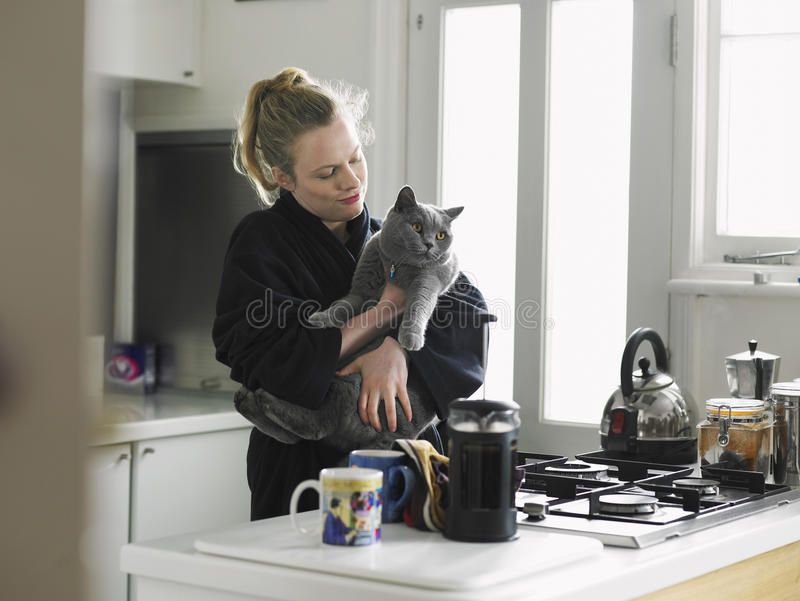 Woman Holding Cat In Domestic Kitchen stock photography