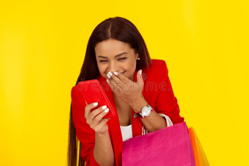 Woman holding cellphone in hand examining it with surprised face, big eyes isolated yellow backdrop royalty free stock photography