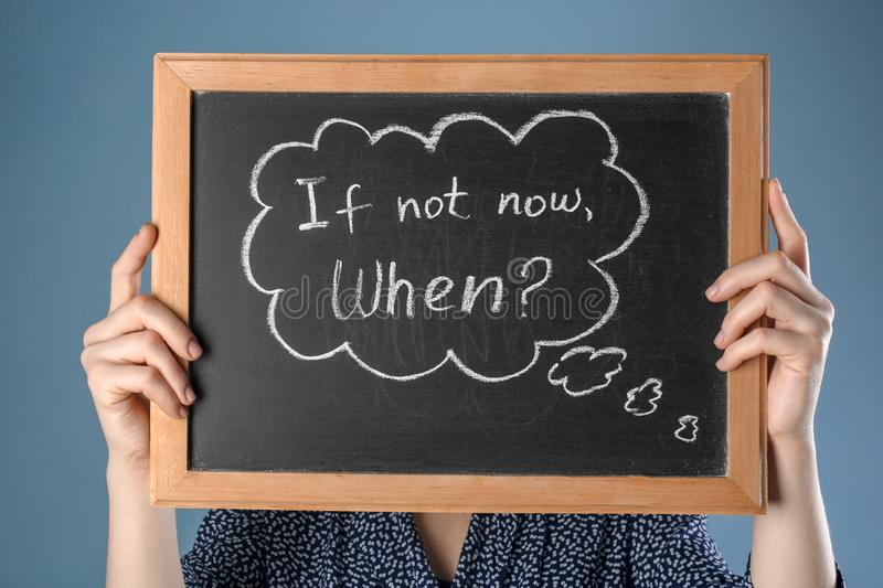 Woman holding chalkboard with phrase If not now. When? on color background. Time management concept royalty free stock photo