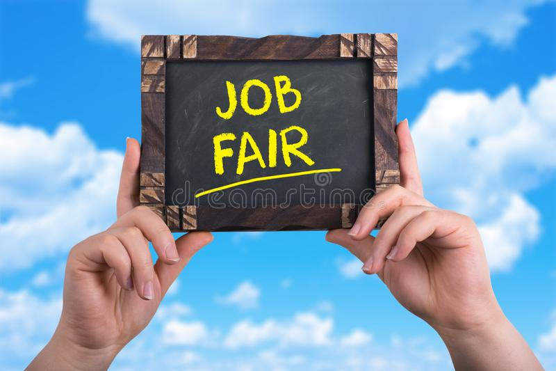 Job fair sign. A woman holding chalkboard with words job fair on blue sky background royalty free stock image