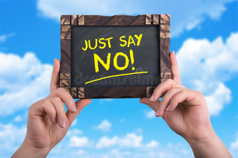 Just say no. A woman holding chalkboard with words just say no on blue sky background stock photography