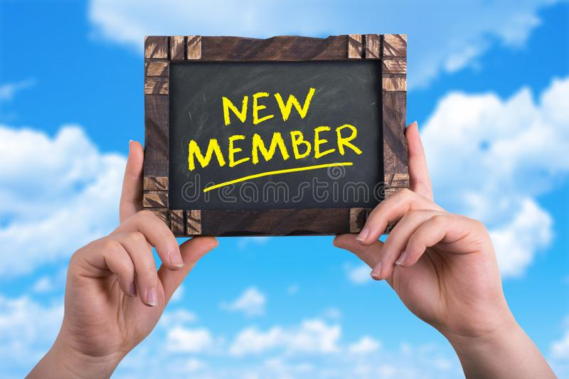 New member sign. A woman holding chalkboard with words new member on blue sky background stock image