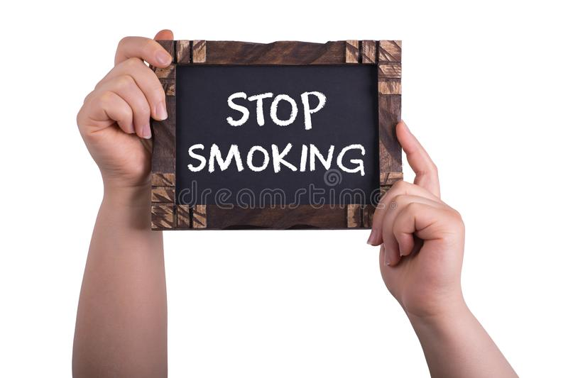 Stop smoking sign. A woman holding chalkboard with words stop smoking isolated on white background stock images