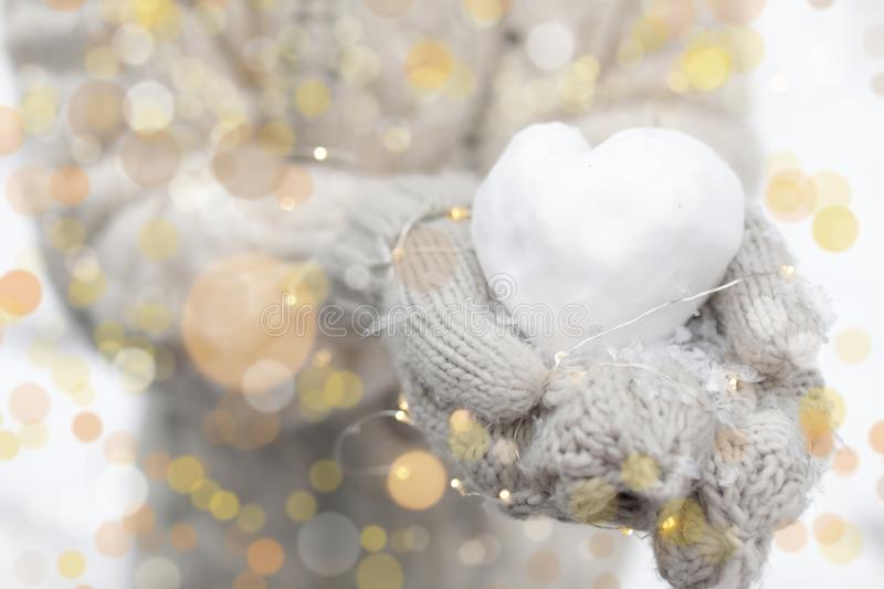 Woman holding Christmas lights and heart made of snow. Closeup stock photo