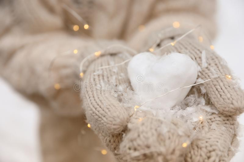 Woman holding Christmas lights and heart made of snow. Closeup stock images