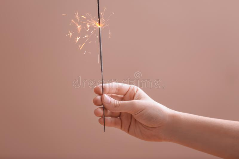 Woman holding Christmas sparkler on color background stock image