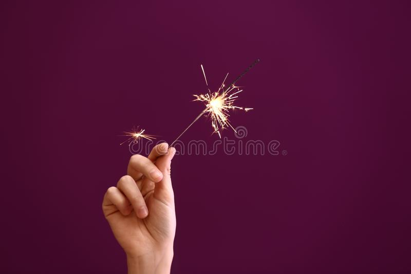 Woman holding Christmas sparkler on color background stock photo