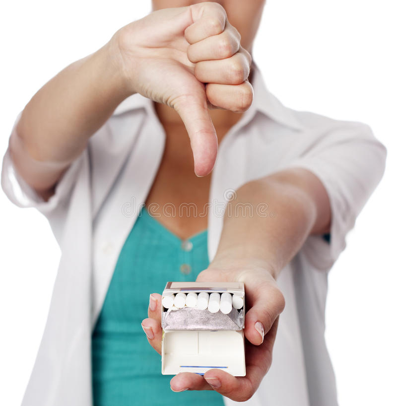 Woman holding cigarettes and showing thumb down. Young woman holding cigarettes and showing thumb down over white backgroud stock image
