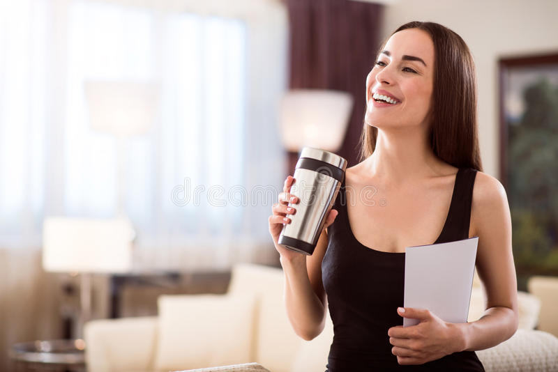 Woman holding clean paper and thermo mug. Today is a good day. Beautiful delighted young woman looking aside while holding a clean sheet of paper and a thermo stock images