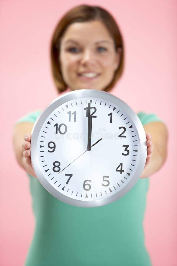 Woman Holding Clock Showing 12 O Clock