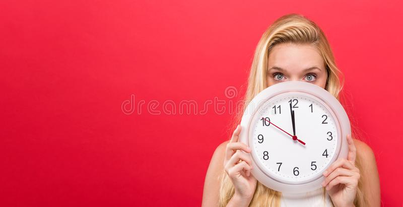 Woman holding clock showing nearly 12. Young woman holding a clock showing nearly 12 royalty free stock photography