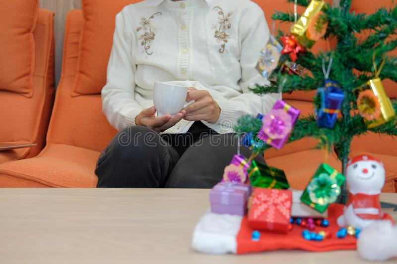 Woman holding coffee cup with gift box christmas tee. xmas new y. Woman wearing cream cardigan holding coffee cup with gift box christmas tee. xmas new year stock image