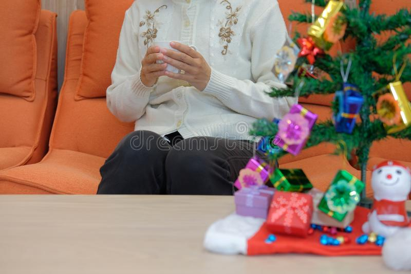 Woman holding coffee cup with gift box christmas tee. xmas new y. Woman wearing cream cardigan holding coffee cup with gift box christmas tee. xmas new year stock photos