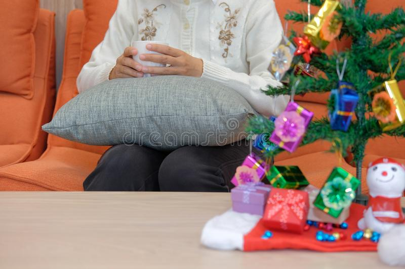 Woman holding coffee cup with gift box christmas tee. xmas new y. Woman wearing cream cardigan holding coffee cup with gift box christmas tee. xmas new year royalty free stock image