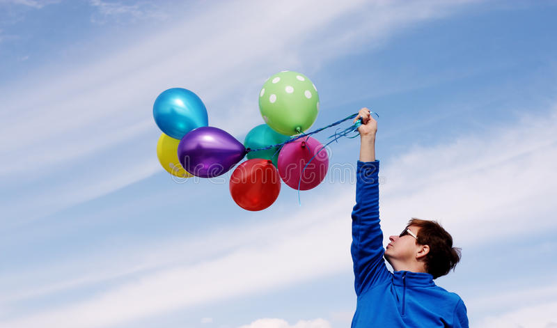 Woman holding colorful balloons. Outside royalty free stock photography
