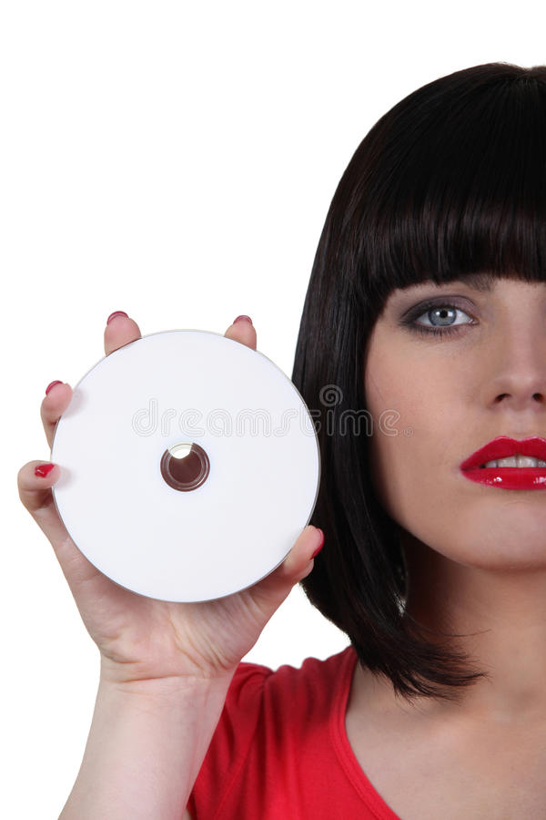 Woman holding a compact disc. Closeup of a woman holding a compact disc stock photos