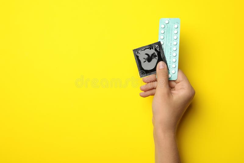 Woman holding condom and birth control pills on yellow, top view with space for text. Safe sex stock photography