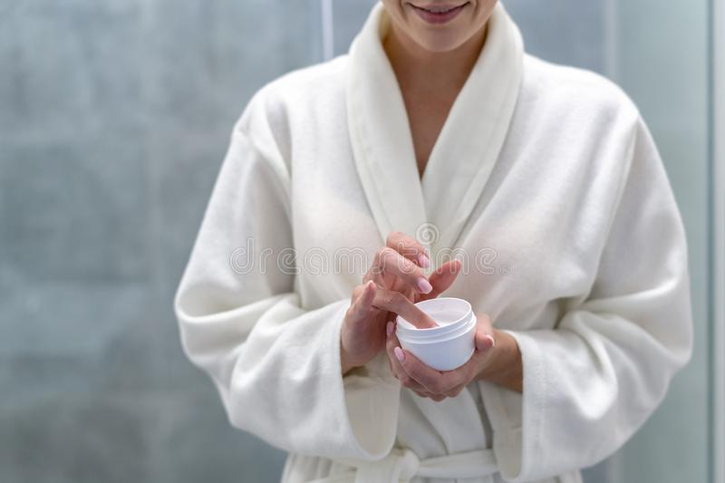 Woman holding cream in hands, standing at bathroom royalty free stock image