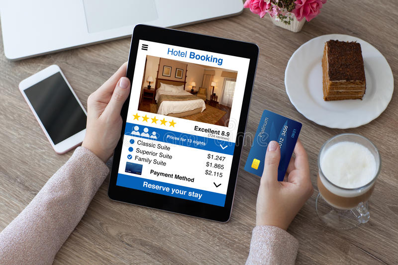 Woman holding credit card and computer tablet app hotel booking royalty free stock photos