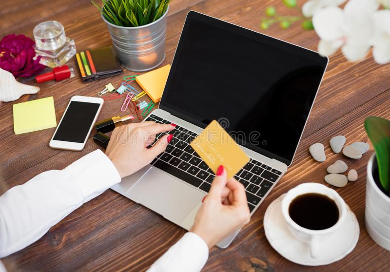 Woman holding credit card in front of laptop stock photo