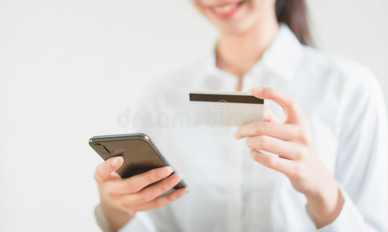 Woman holding credit card with shopping online on smartphone and enter the payment code for the product. Woman holding credit card with shopping online on royalty free stock photography