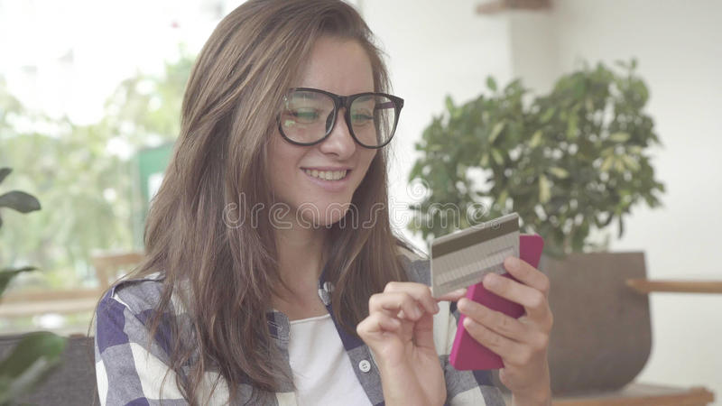 Woman holding a credit card and using cell phone for online shopping. Caucasian model royalty free stock photography