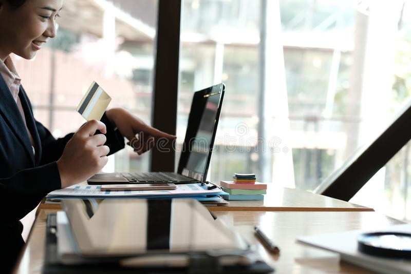 woman holding a credit card and using computer for online shopping at cafe. businesswoman purchase goods from internet at office. royalty free stock images