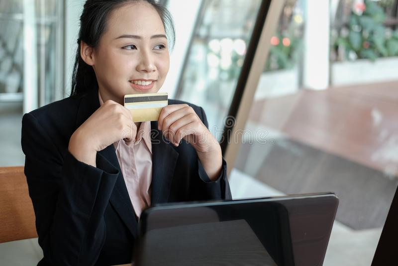 woman holding a credit card and using computer for online shopping at cafe. businesswoman purchase goods from internet at office. stock photography