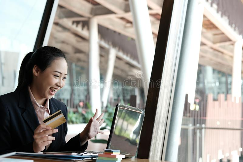 woman holding a credit card and using computer for online shopping at cafe. businesswoman purchase goods from internet at office. stock photo