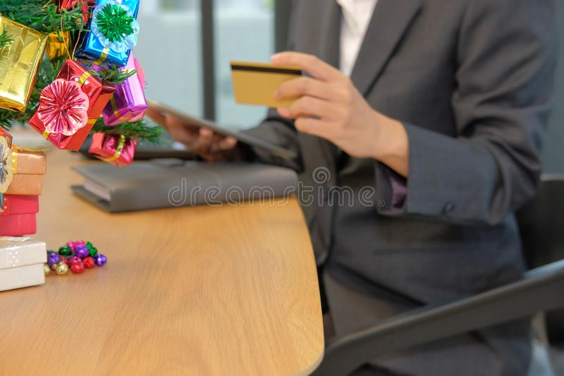 woman holding credit card using tablet for online shopping. businesswoman buying on internet during christmas holiday royalty free stock image