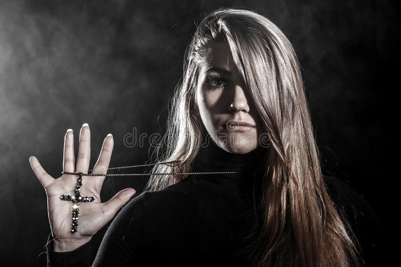 Woman holding a cross on her palm stock images
