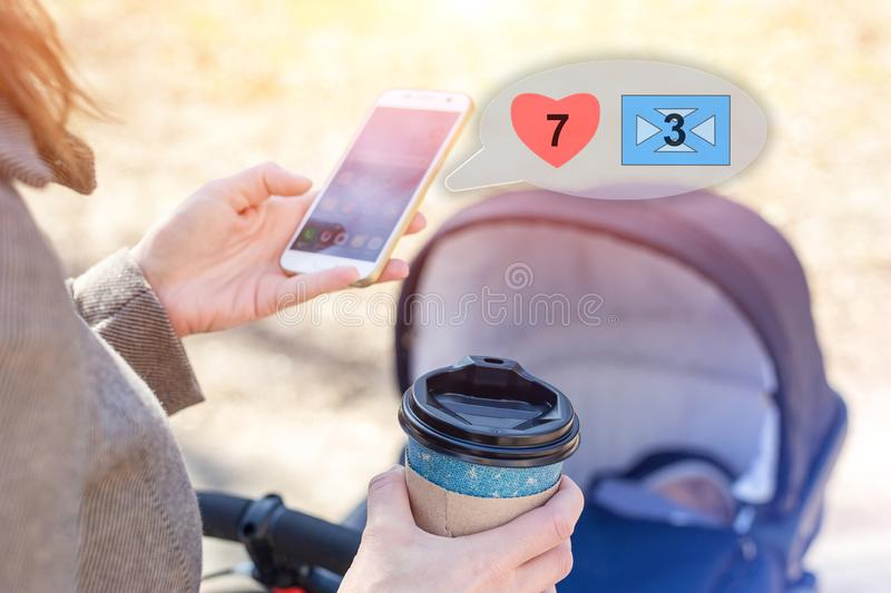 Woman holding cup of coffee to go and using smartphone during walk with baby carriage. Browsing social media, likes and messages. Modern young business woman stock photos