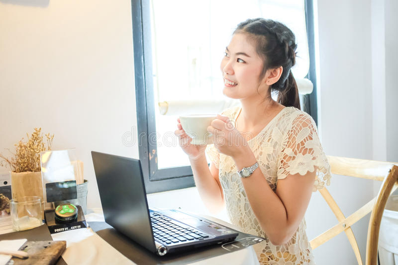 Woman holding cup of coffee use social networking with laptop stock photography