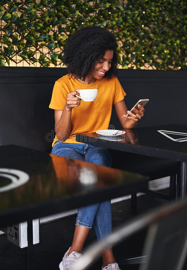 Woman holding cup of coffee using mobile phone in cafe stock photography