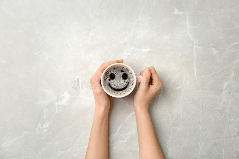 Woman holding cup of delicious hot coffee with foam and smile on light background, top view. Happy morning, good mood. Inspiration stock photos