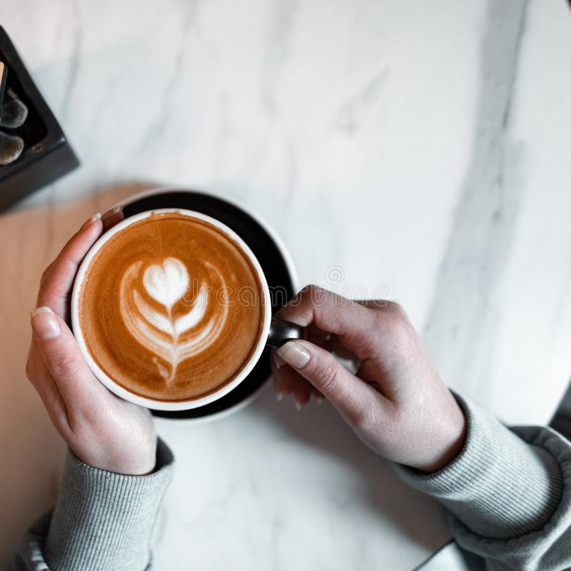 Woman is holding a cup with a delicious hot latte in a vintage coffee shop. Coffee gourmet. Good morning. View from above. Woman is holding a cup with a royalty free stock photography