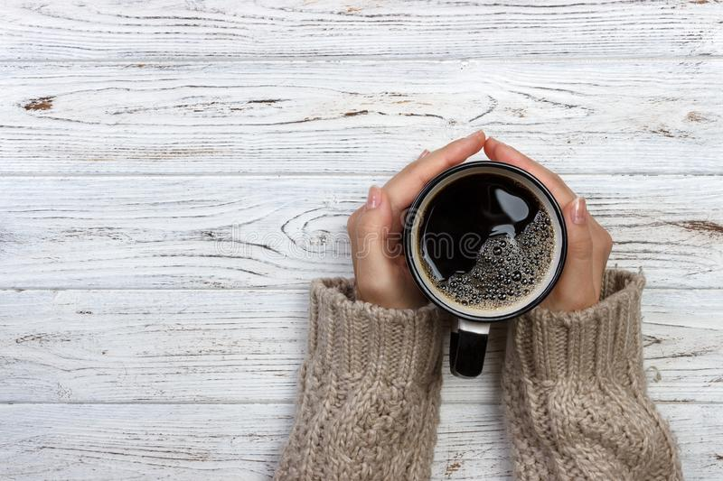 Woman holding cup of hot coffee on rustic wooden table, closeup photo of hands in warm sweater with mug, winter morning concept, t royalty free stock photography