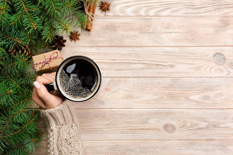 Woman holding cup of hot coffee on rustic wooden table. hands in warm sweater with mug, winter morning or christmas concept, top v. Iew stock photos